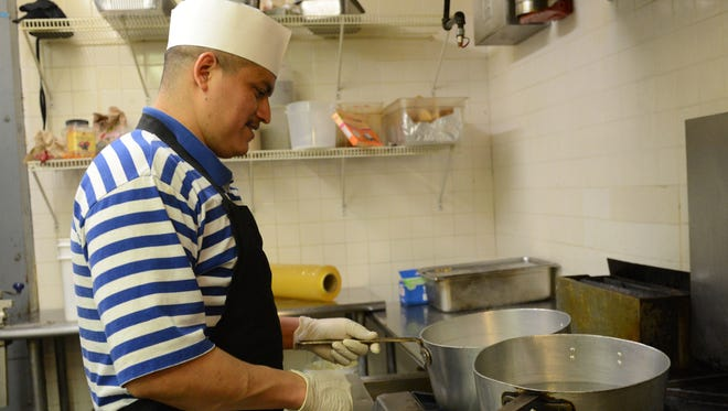 Joan Cruz, a chef at Casa Fiesta in Fremont, is busy in the kitchen on Wednesday.