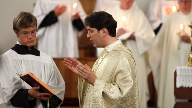 The Rev. Cory Mayer, parish administrator at Ave Maria, presides over Easter Vigil Mass in April. Mayer also serves as vocations director for the Diocese of Venice.