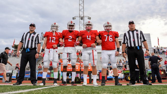 Colerain captains Gunnar Leyendecker (12), Javon Hicks (2), Dan Bolden (4) and Nick Kroeger (76) walk out for the coin flip against Lakota East, Friday, Oct. 6, 2017