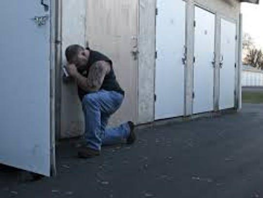 Jamie Bowman prays outside a storage unit in Redding