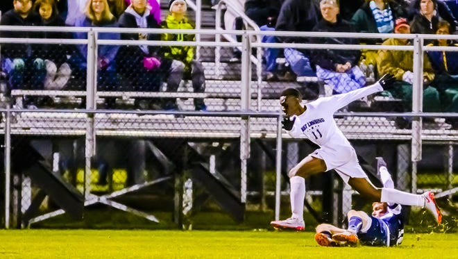 Sam Lebbie ,top, of East Lansing leaps over a Grand Ledge defender as he pursues the ball during their CAAC Gold Cup Final game last season in Holt. Lebbie, who earned Division 2 all-state honors last season, is expected to be one of the CAAC Blue's standout players in 2016.