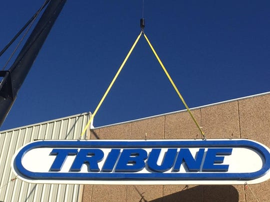 The Great Falls Tribune's restored sign is lifted back into place Friday.