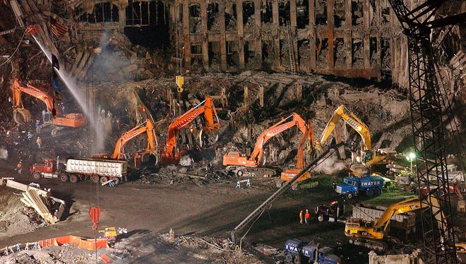 In this Nov. 7, 2001 file photo, workers and heavy machinery continue the cleanup and recovery effort in front of the remaining facade of 1 World Trade Center at ground zero in New York City.