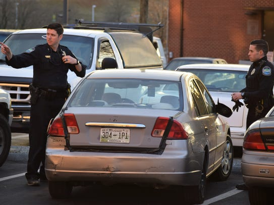 A Knoxville Police Department officer gestures toward