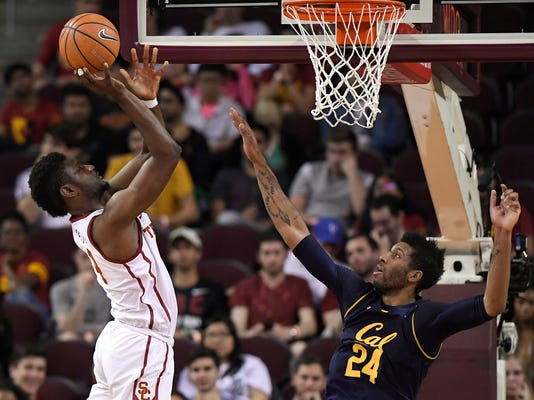 Southern California forward Chimezie Metu, left, shoots as California forward Marcus Lee defends during the first half of an NCAA college basketball game, Sunday, Jan. 28, 2018, in Los Angeles. (AP Photo/Mark J. Terrill)