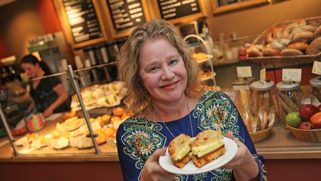 Brew Ha Ha! owner Alisa Morkides, holds up a Florentine chorizo sausage breakfast sandwich.