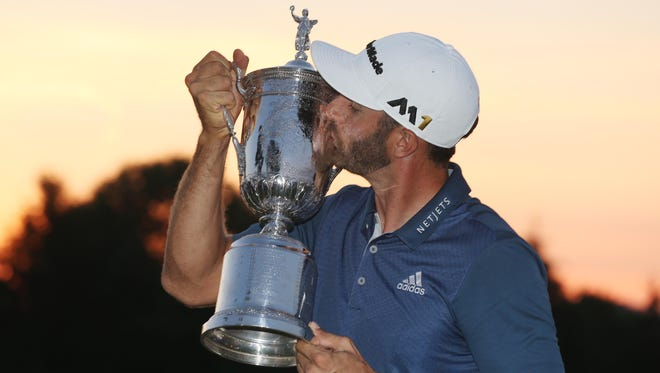Dustin Johnson poses with the championship trophy after winning the U.S. Open at Oakmont Country Club on June 19.