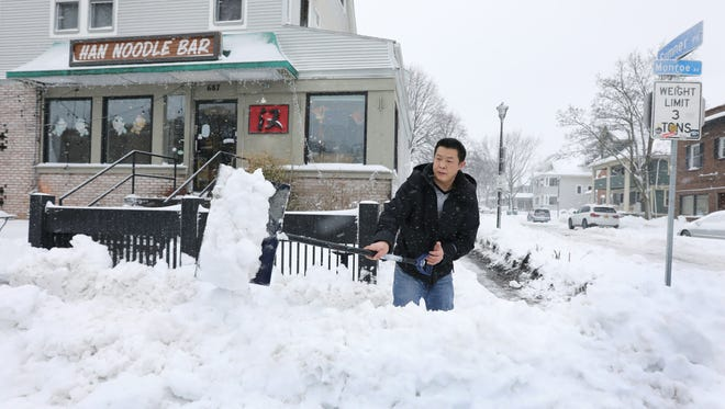 Zhang Fayuan clears the sidewalk and entrance to Han Noodle Bar where he works on Monroe Avenue during a snowstorm.