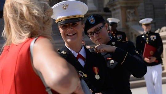 Marine Corps 2nd Lt. Elizabeth Vincent, center, talks to her mother,Jennifer Kiel, as her sister, Emily Vincent, adjusts her dress blues Friday at the Capitol in Lansing.