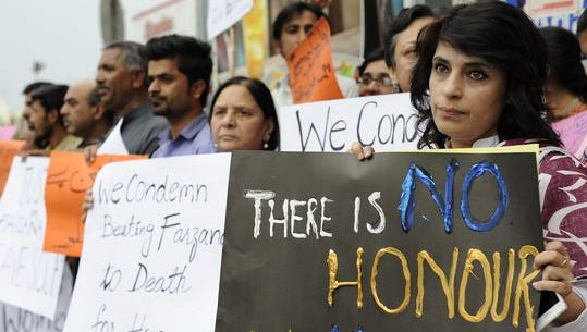 Civil society activists carry placards during a protest in Islamabad on May 29, 2014, against the killing of Farzana Iqbal who was stoned to death by her family for marrying against their wishes.