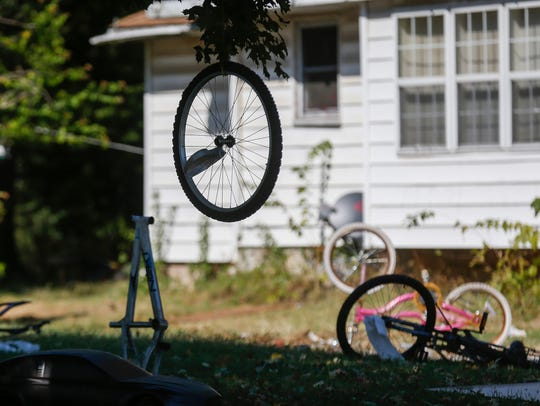 A bicycle tire hung from a tree in front of a house
