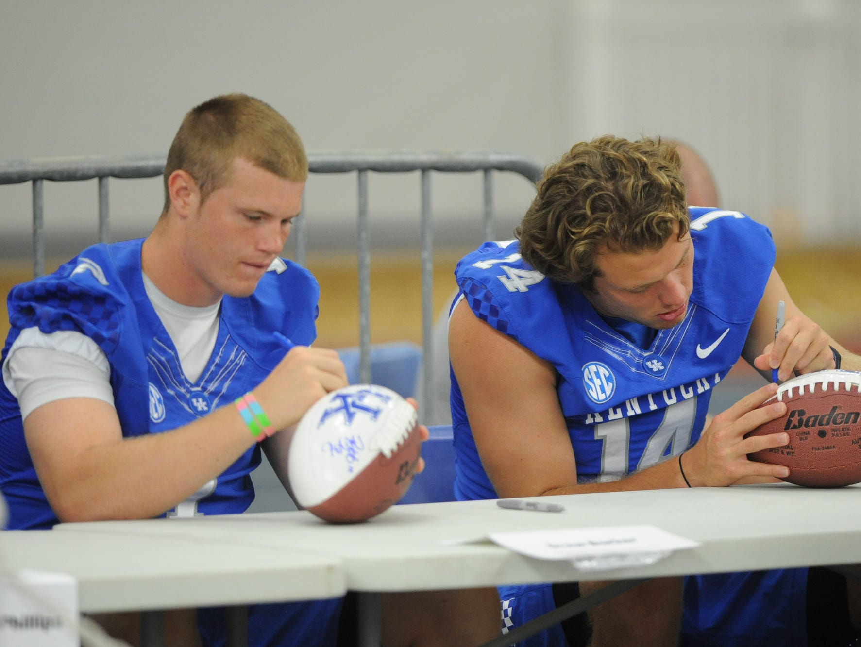 Redshirt freshman QB Drew Barker and junior QB Patrick Towles autograph footballs during the University of Kentucky Football fan day at the Nutter Field House in Lexington, Ky., on Saturday August 8, 2015.