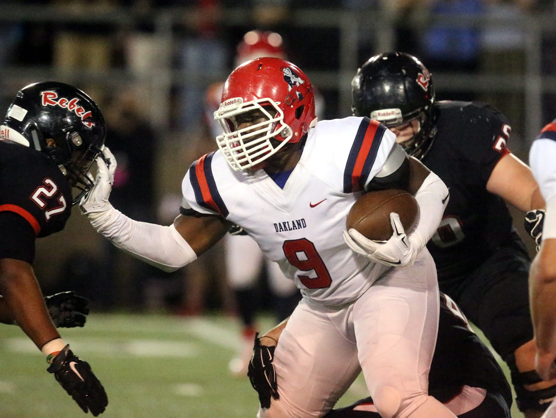 Oakland's Ty Nix (9) runs the ball as Maryville's TD Blackmon (27) moves in for the tackle Friday.