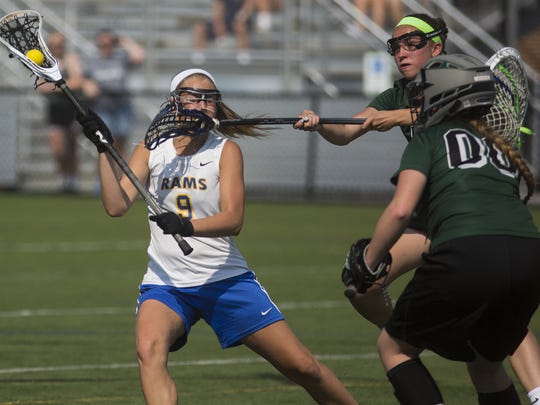 Kennard-Dale's Megan Halczuk, left, moves in for a shot on Pine-Richland goalkeeper Abigail Levier (No. 00). Kennard-Dale defeated Pine Richland 12-9 in the first round of the PIAA Girls' Lacrosse State Championships at Cumberland Valley High School in Silver Spring Township on Wednesday.