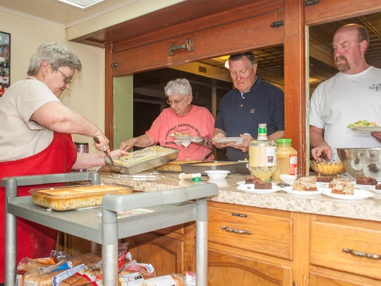 Carlotta Pinney, left, of Christ Fellowship Bible Church, serves dinner to United Methodist Committee of Relief volunteers helping to rebuild homes in Crisfield that were damaged by Hurricane Sandy.