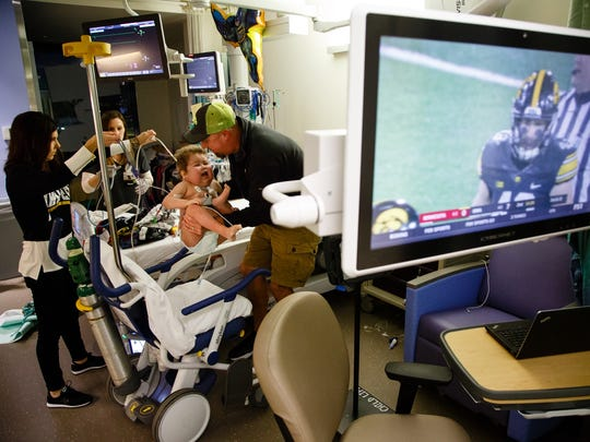 After watching the wave and with the second quarter barely underway, 6-year-old Will Kohn is transferred back to his bed to begin dialysis for the next 17 hours at the UI Stead Family Children's Hospital on Saturday, Oct. 28, 2017, in Iowa City.