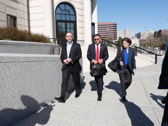 Aaron Troodler, left, leaves the Federal Courthouse