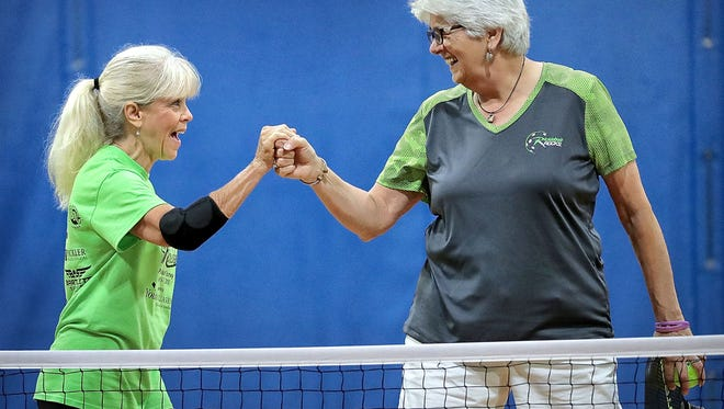 Sheila Brandenburg (left) and Ginny Whitley celebrate after scoring a point while playing pickleball at the Singleton Community Center Wednesday morning.