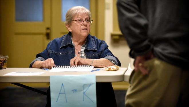Today is election day in Lebanon. Poll worker Helen Stewart checks in a voter at Tabor Church in Lebanon Tuesday.