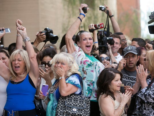 Mikal Ann Dillon of Phoenix raises her arm in the air as she reacts May 8, 2013, to a guilty verdict on first degree murder for Jodi Arias outside of Maricopa County Superior Court in Phoenix. Dillon had attended in person nearly every day of the trial.