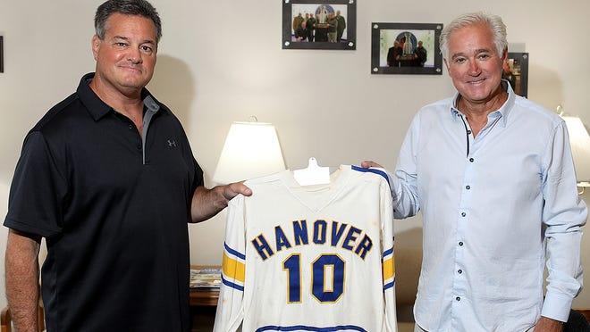 Jon Frattasio, left, and Dr. Jay Parker hold Jay's hockey jersey, which he wore while playing hockey for Hanover High when he played there from 1972-1975. Jon found the jersey at the Hanover Police Boys Club with his brother, Adam, and wanted to surprise his friend.