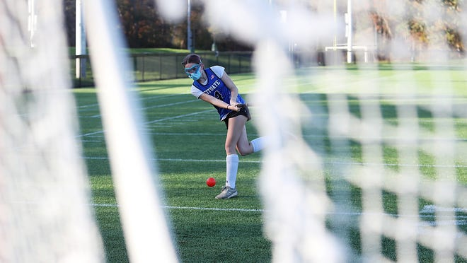 Freshman Ava von Freymann of the Scituate field hockey team is framed by the netting of a lacrosse goal during a shooting drill at practice at the high school on Wednesday, Oct. 21, 2020.