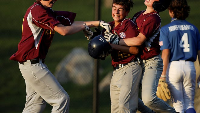 Jack Reyes is embraced by Matt Duddy, right, and Danny Civello, left, after scoring the winning run in the bottom of the seventh inning after a wild pitch to give Weymouth the 4-3 win over Plymouth Babe Ruth All Stars 13þÄôs at Libby Field on Tuesday, Sept. 8, 2020.
