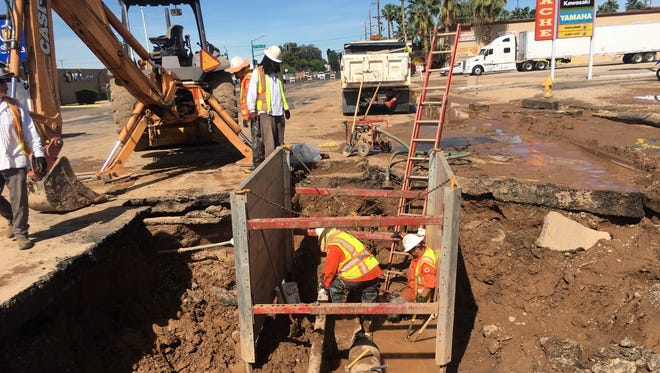 Crews with the Phoenix Water Services Department work to fix a water main break on Camelback Road on April 26, 2017.