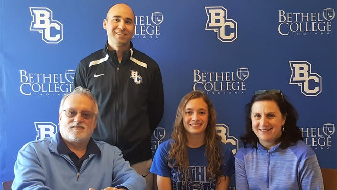 Hartland's Michelle Moraitis is flanked by her father, Robert; mother, Nanette; and Bethel College women's basketball coach Eric Gingerich as she signs a national letter of intent.