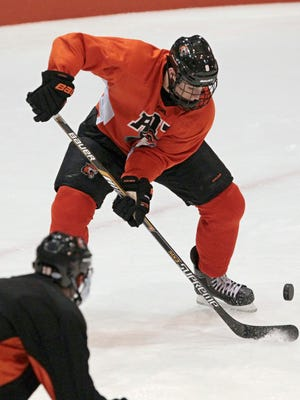 RIT captain Matt Garbowsky corals a bouncing puck during their practice Wednesday, Oct. 8, 2014, at the Polisseni Center at RIT in Henrietta.