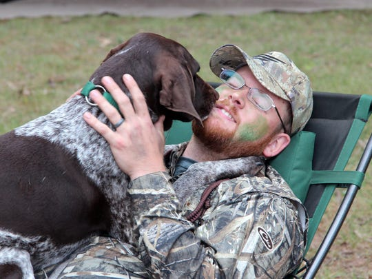Chris Wiberg of North Branch, Minn., gets a lick from his German shorthaired pointer during a break Sept. 24, opening day of the 2016 Wisconsin waterfowl hunting season.