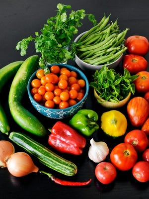 Roughly clockwise from bottom left: Onions, cucumbers, sweet sun gold tomatoes, cilantro, green beans, spicy basil, tomatoes tomatoes tomatoes, squash, garlic, bell peppers, hot pepper, zucchini. Photo by Chris Dunn.