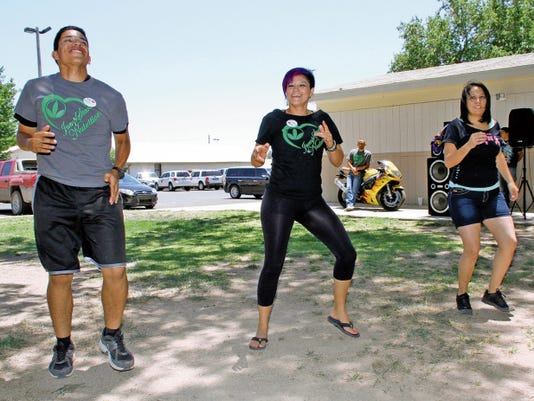Bill Armendariz - Headlight Photo   From left, Sergio Quezada, Iris Nevarez and Marisol Bejarano dance to the Zumba beat during Saturday's fund-raising carnival for Christina Sotelo and her battle against cancer. The trio fo Zumba dancers represent Jump Start Nutrition on Cody Road.