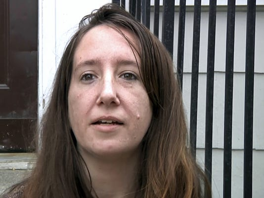 In this Oct. 6, 2015, still frame from video, Chelsea Cole sits on the steps of her home during an interview in Rutland, Vt. Cole, 31, a former nursing assistant, said she started drinking a lot when she was 18, using pills when she was 25, and heroin when she was 28. She's been clean for two years and said she couldn't have done it without the support systems Rutland created over the last several years. Cole now works at the Turning Point Center of Rutland, an organization that helps people in Rutland recover from addictions. (AP Photo/Michael Hill)