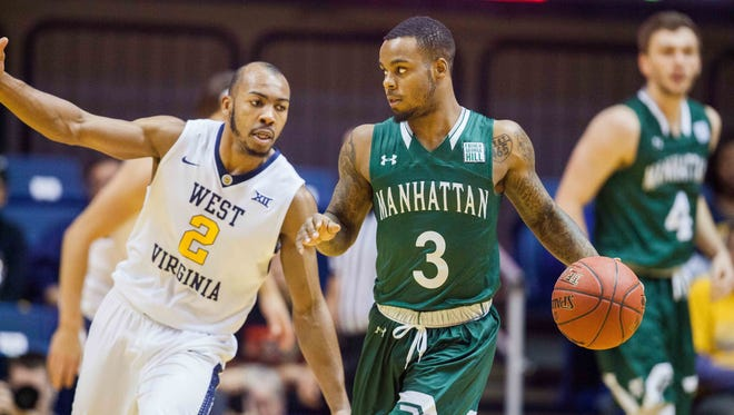 Manhattan Jaspers guard Zavier Turner (3) dribbles while guarded by West Virginia Mountaineers guard Jevon Carter (2) during the first half at WVU Coliseum.
