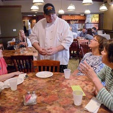 Chef Mark Hincker of Station 885 chats with crawlers Dot Balogh of Plymouth, Sue Tamaroglio of Westland and Carol Vandenberg of Canton Township. The chef served up pork sliders with baked beans and cole slaw.