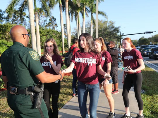 Students return to Marjory Stoneman Douglas High School on Wednesday in Parkland, Fla.    Andrea Melendez/The News-Press Broward County police officer Bernard Hilson greets students as they walk to Marjory Stoneman Douglas High School on Wednesday, Feb. 28, 2018.  Andrea Melendez/The News-Press [Via MerlinFTP Drop]