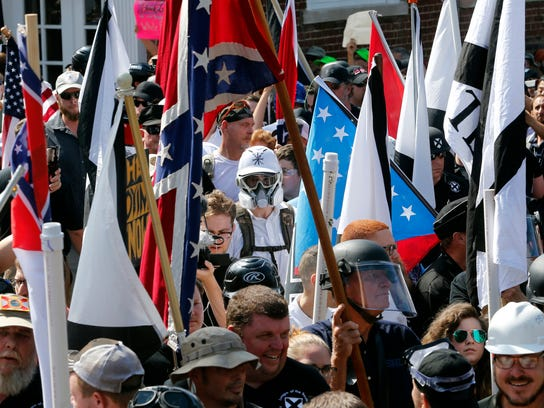 "FILE- In this Saturday, Aug. 12, 2017, photo white nationalist demonstrators walk into the entrance of Lee Park surrounded by counter demonstrators in Charlottesville, Va. The Detroit Lions said Tuesday, Aug. 15, that they ""detest and disavow"" any use of their logo associated with the event Saturday in Charlottesville. A photo taken at the demonstration showed someone with a logo similar to the one the Lions use, although it was blue and red and had stars on it. (AP Photo/Steve Helber, File)"