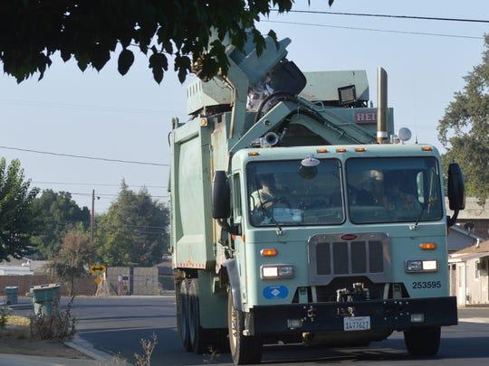A trash truck picks up a can on Watson Street in Visalia.