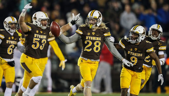 Wyoming safety Andrew Wingard celebrates with teammates after one of his five interceptions last season. The Cowboys led the nation in a takeaways in 2017 with 38.