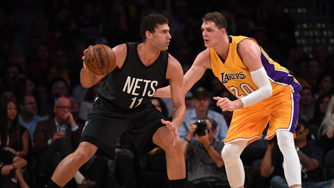 Brooklyn Nets center Brook Lopez (11) is defended by Los Angeles Lakers center Timofey Mozgov (20)  at Staples Center on Tuesday night.