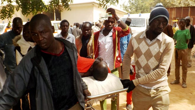 A man injured in a suicide blast is transported at a hospital in northeast Nigerian town of Potiskum, Jan. 12, 2015. Four people were killed and 46 injured when two girls detonated outside a mobile phone market  Jan. 11.