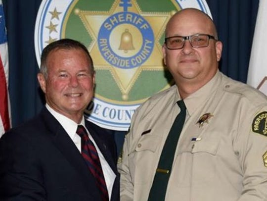 Investigator Robert Cornett, right, a Riverside County sheriff's department employee who was implicated in the 2015 cheating scandal, poses with Sheriff Stan Sniff while being promoted to the position of master investigator in November 2016,
