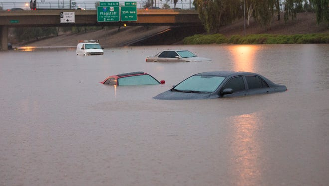 Cars were stuck in flood waters on Interstate 10 east at 43rd Ave. after monsoon rains flooded the freeway in Phoenix Sept. 8, 2014.