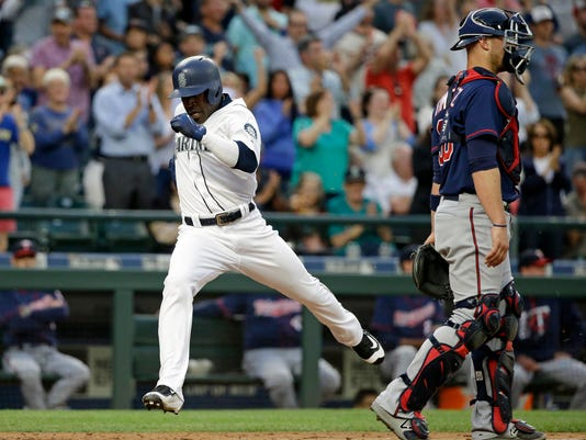 Seattle Mariners' Guillermo Heredia, left, scores as Minnesota Twins catcher Chris Gimenez looks away in the fourth inning of a baseball game Tuesday, June 6, 2017, in Seattle. (AP Photo/Elaine Thompson)