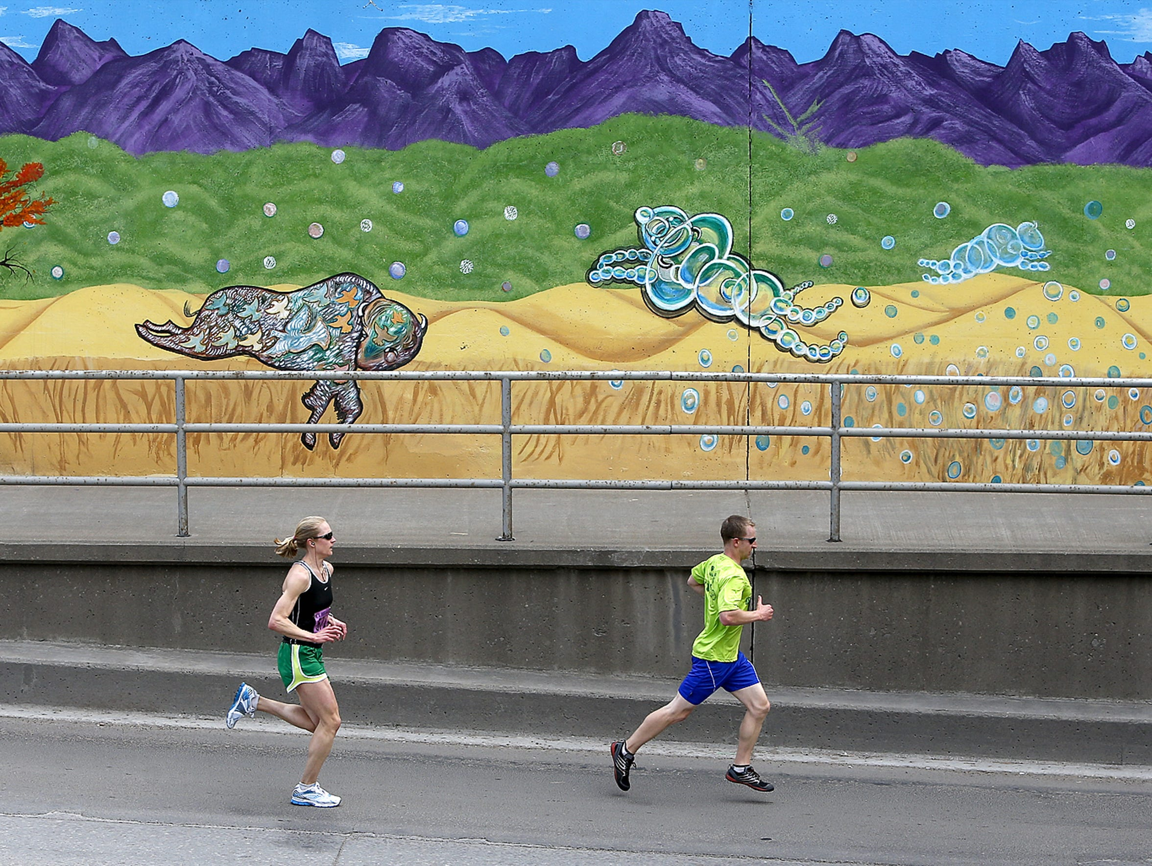 Runners pass the 1st Avenue North mural in Great Falls.