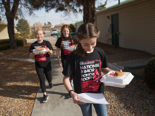 Hermosa Middle School students Emily Black, left, Alyssa Taft and Bria Cohen deliver meals to residents of the Apple Ridge Apartments Thursday in Farmington.
