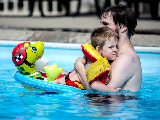 Max makes a face realizing how cold the water is after begging his new parents to take him and his sibling swimming on a chilly morning. Brett, his new father, just laughs as he holds him close in the pool.