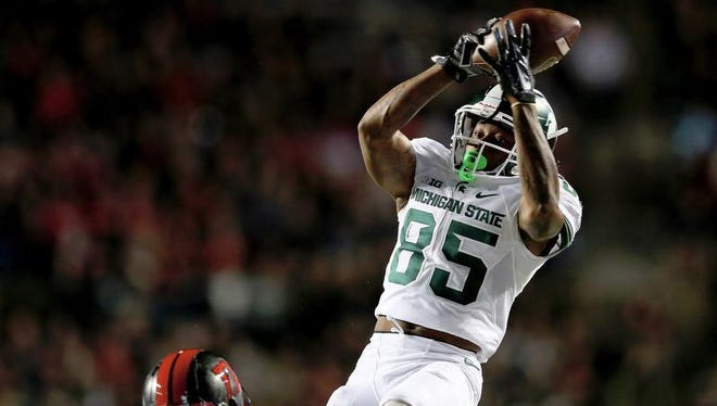 Macgarrett Kings Jr. #85 of the Michigan State Spartans makes the catch in the second quarter as Isaiah Wharton #11 of the Rutgers Scarlet Knights defends in the second quarter on October 10, 2015 at High Point Solutions Stadium in Piscataway, New Jersey.