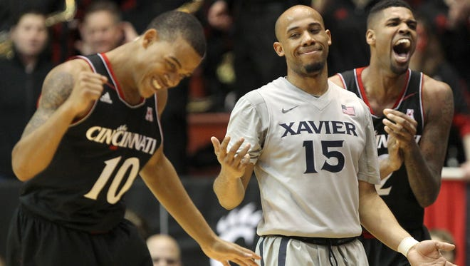From left: Cincinnati Bearcats guard Troy Caupain (10), Xavier Musketeers guard Myles Davis (15) and Cincinnati Bearcats forward Octavius Ellis (2) react after a turnover during the second half, Wednesday, Feb. 18, 2015, at Fifth Third Arena.